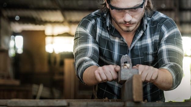 Un menuisier utilise une raboteuse pour gratter la surface en bois.