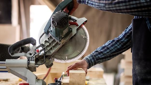 Menuisier en vêtements de travail faisant des boiseries en menuiserie. propriétaire de petite entreprise coupé sur planche de bois