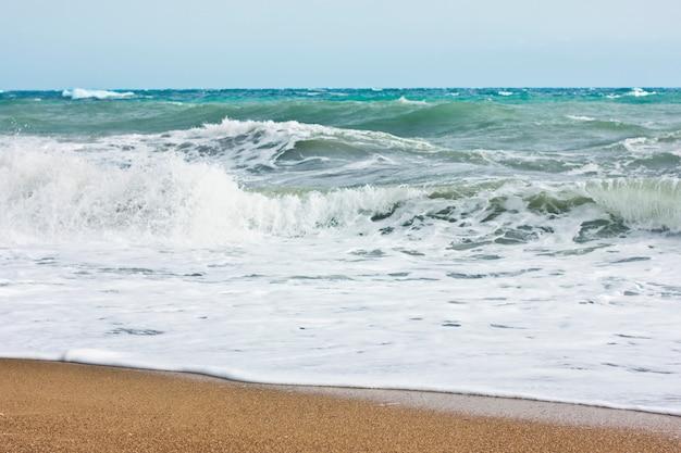 Mer agitée et ciel bleu, écume de mer blanche sur une plage de sable jaune.