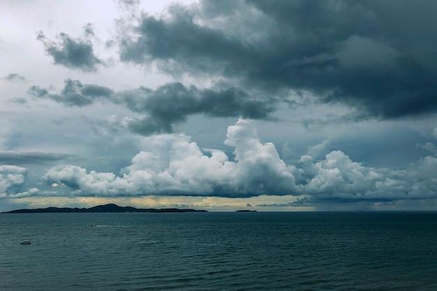 Mer avec des bateaux au loin sous un ciel nuageux