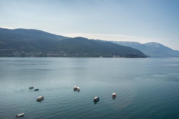 Mer avec des bateaux sur elle entourée de collines couvertes de verdure sous la lumière du soleil