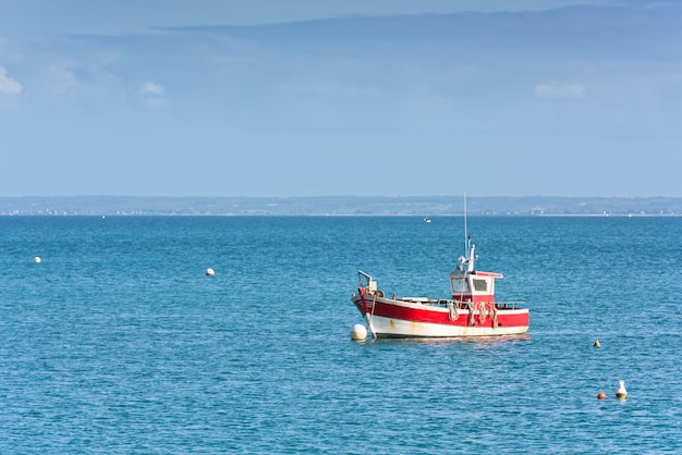 Mer bleu vif et un bateau de pêcheur en bretagne, france