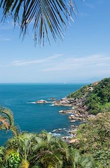 Mer bleue et côte rocheuse dans une journée ensoleillée à l'île d'ilhabela, brésil