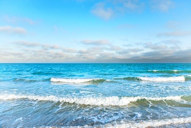 Mer bleue avec des vagues, de la mousse et des nuages blancs dans le ciel