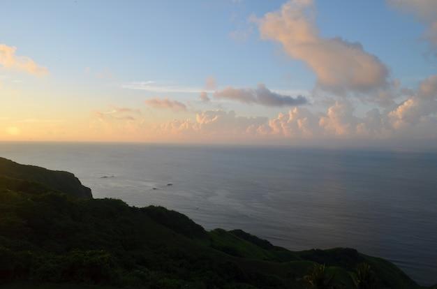 Mer calme entourée de collines et de verdure au coucher du soleil sous un ciel bleu