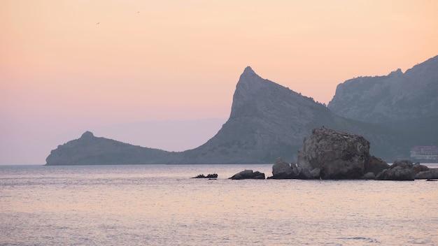Mer calme et rochers sombres au coucher du soleil. paysage marin dramatique. calme. 4k uhd