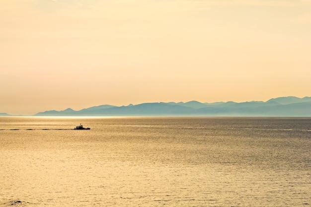 Mer, collines et bateau au coucher du soleil