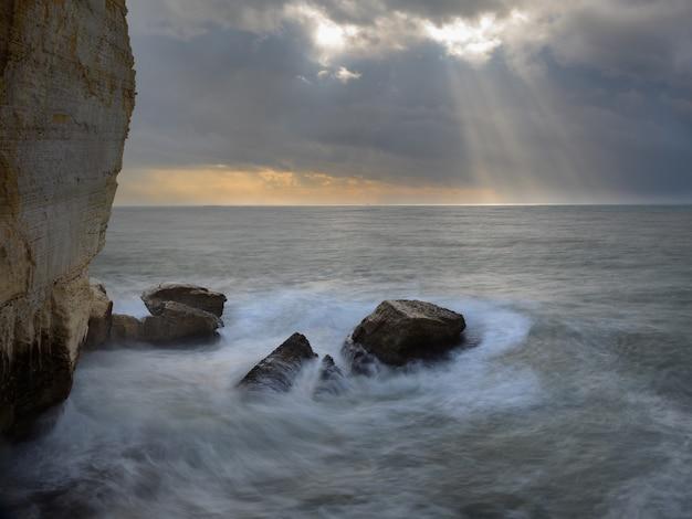Mer déchaînée avec des pierres et des falaises sous un ciel gris orageux et des rayons de soleil