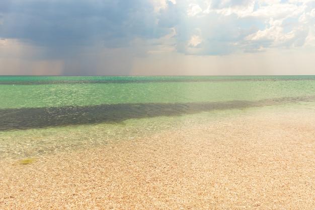 Mer d'été belle plage tropicale exotique. vert émeraude de la mer et ciel bleu vif avec des nuages avec la lumière du soleil. paysage marin d'été, eau turquoise de l'océan, île idyllique ou bannière de plage