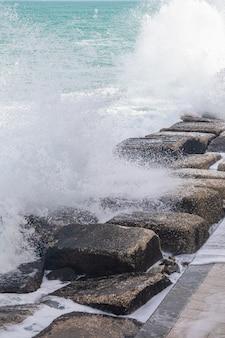 Mer ondulée saupoudrant de gouttelettes sur les pierres