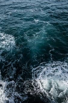 Mer orageuse, surface de l'eau d'un bleu profond avec de la mousse et des vagues