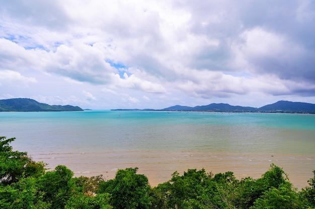 Mer de paradis tropical avec petite île et cadre d'arbres au premier plan