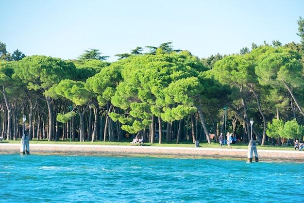 Mer et parc verdoyant avec des marcheurs sur la digue à venise