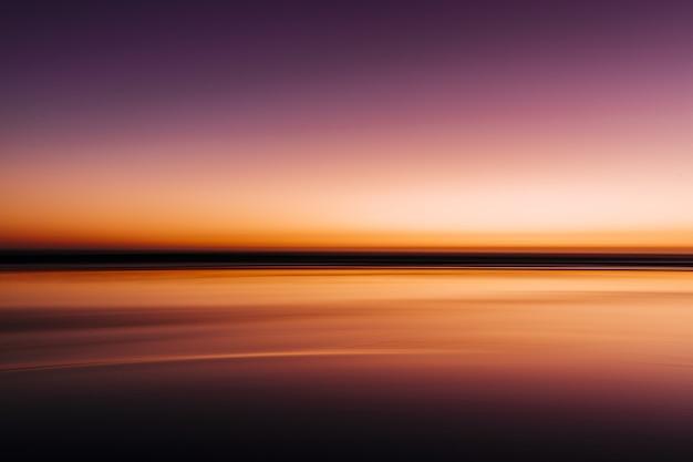 Mer pendant un coucher de soleil coloré avec une longue exposition
