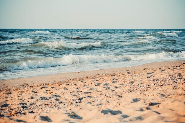 La mer et la plage de sable, avec des sommets blancs de vagues clapotant sur le rivage, le filtre