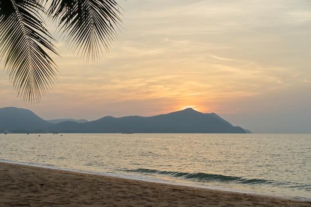 Mer et plage le soir. soleil tombant derrière la montagne.