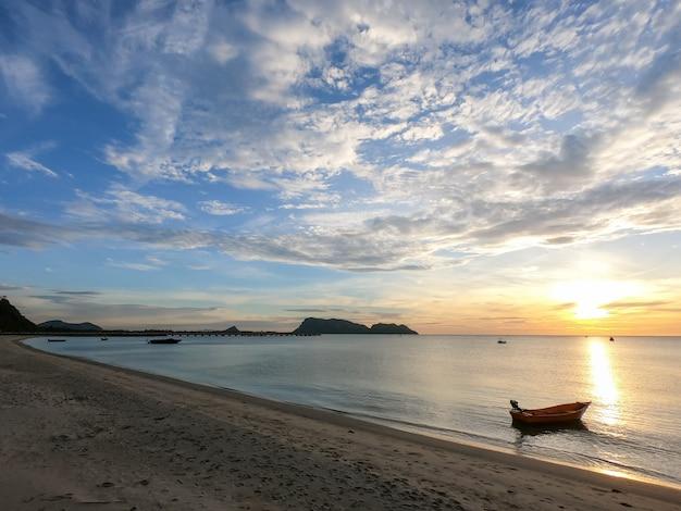 Mer en saison estivale au lever du soleil avec petit bateau et ciel nuageux.
