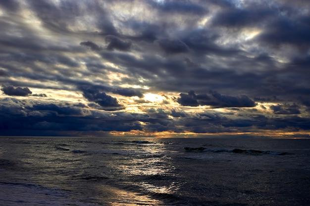 Mer spectaculaire et rayons de soleil avec des nuages sombres