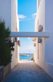 La mer à travers deux bâtiments blancs