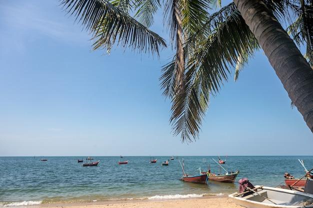 Mer tropicale avec cocotiers et bateau de pêche sur la plage