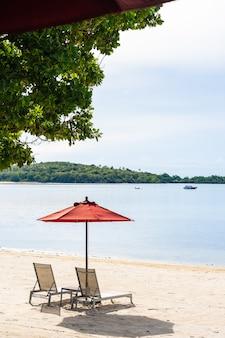 Mer tropicale en plein air de plage tropicale avec chaise de parasol et terrasse de salon autour de là sur le ciel bleu de nuage blanc