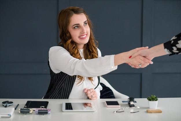 Merci. collègue félicitation poignée de main. femme souriante sur un lieu de travail parfaitement organisé. .