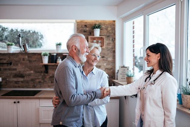 Merci docteur! senior couple saluant une femme médecin.