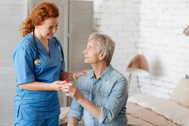 Merci de m'aider. délicate femme professionnelle formée prenant soin d'un homme âgé tout en lui rendant visite et en apportant les médicaments nécessaires