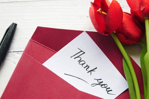 Merci message et enveloppe sur table en bois