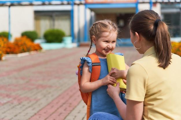 La mère accompagne l'enfant à l'école.