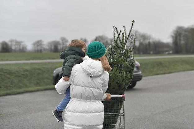 La mère a acheté un arbre de noël au marché