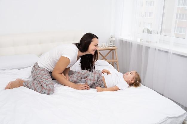 Mère adulte chatouille sa petite fille active au lit à la maison, activité de loisirs avec les enfants.