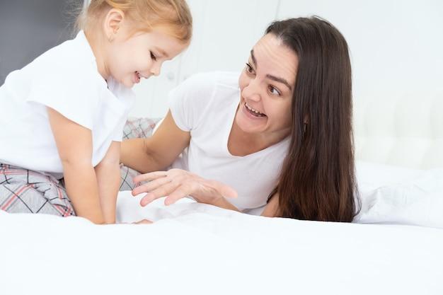 Mère adulte joue avec sa petite fille active au lit à la maison, s'amuse, activité avec les enfants.