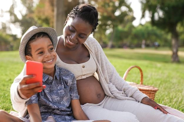 Mère africaine et fils métis prenant un selfie avec un téléphone portable au parc de la ville. une femme enceinte noire profite d'un pique-nique avec un enfant en plein air