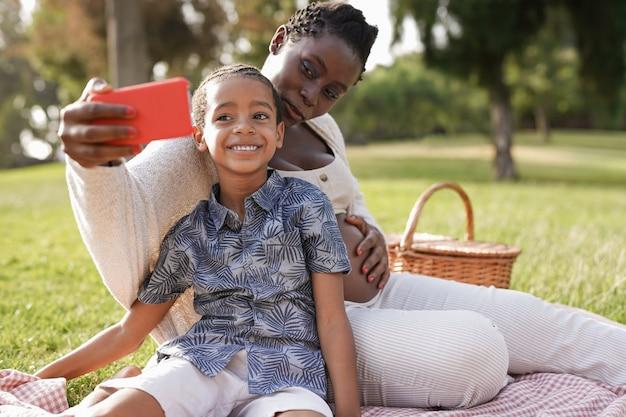Une mère africaine et un fils métis prenant un selfie avec un téléphone portable au parc de la ville - une femme enceinte noire profite d'un pique-nique avec un enfant