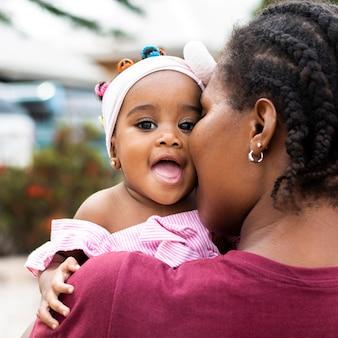 Mère africaine et petite fille se bouchent
