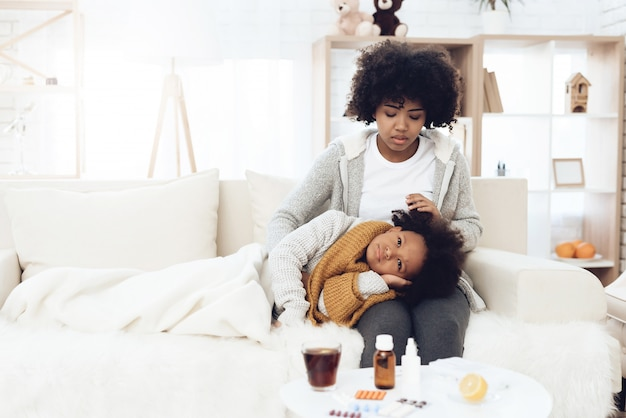Mère afro-américaine avec enfant malade avec la grippe sur ses genoux.