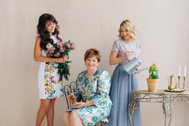 Une mère d'âge moyen avec deux filles, blonde avec un arrosoir et une brune avec un bouquet de lilas.
