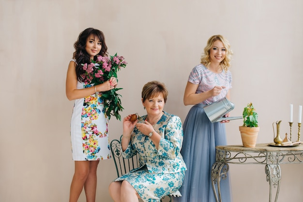 Une mère d'âge moyen avec deux filles, blonde et brune. maman tient du parfum dans ses mains