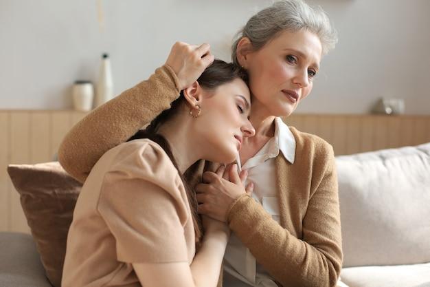 Une mère d'âge moyen embrasse sa fille, réconforte sa fille frustrée et contrariée avec les yeux fermés, touche les joues, assise sur un canapé à la maison. bonnes relations de confiance. notion de famille.