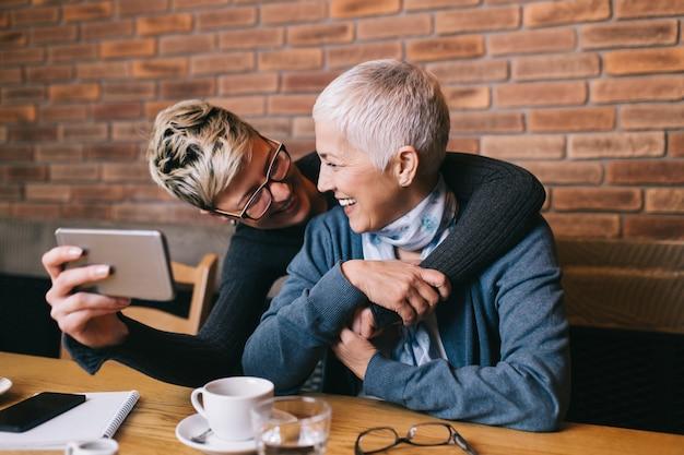 Mère âgée assise dans un café-bar ou un restaurant avec sa fille d'âge moyen et profitant de la conversation.