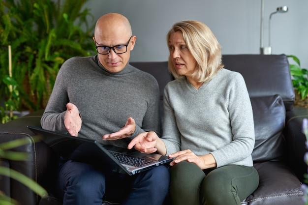 Une mère âgée s'asseoir sur un canapé avec son fils adulte regarder la vidéo sur un ordinateur portable moderne