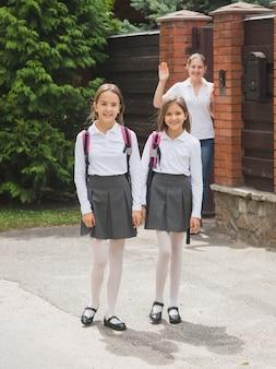 Mère agitant la main à ses filles marchant jusqu'à l'école