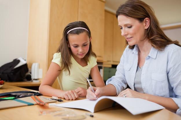 Mère aidant la fille avec ses devoirs
