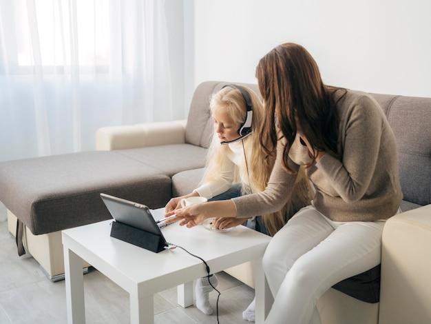 Mère aidant la jeune fille à faire ses devoirs