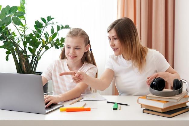 Mère aidant sa fille à faire ses devoirs. le concept de l'enseignement à domicile en quarantaine. du plaisir pendant l'apprentissage à distance