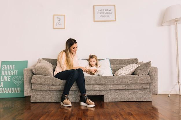 Mère aidant sa fille à lire sur son lit