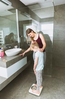 Mère aidant sa fille à peser
