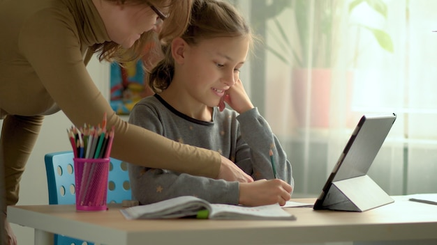 Mère aidant sa fille à terminer ses devoirs