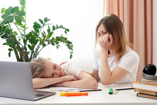 Mère aidant sa fille triste à faire ses devoirs. le concept de l'enseignement à domicile en quarantaine. difficultés de l'apprentissage à distance